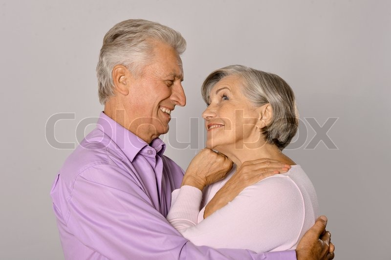 Happy older pair on a gray background, stock photo