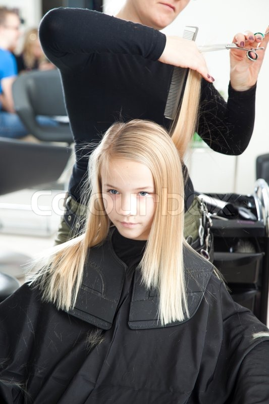 A Young Girl Getting A New Haircut In A ...