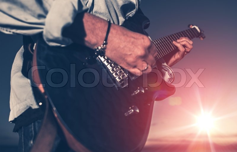 The Guitarist. Guitarist Playing on the Electric Guitar at Sunset. Closeup Photo, stock photo