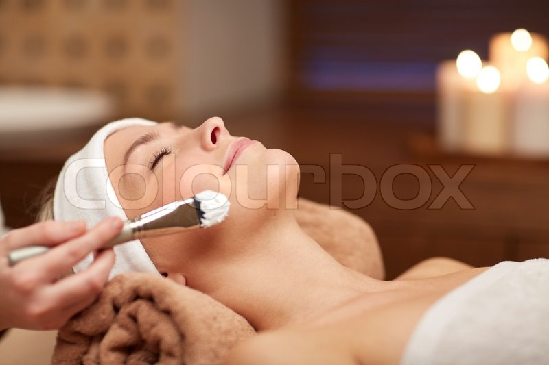 People, beauty, spa, cosmetology and skincare concept - close up of beautiful young woman lying with closed eyes and cosmetologist applying facial mask by brush in spa, stock photo