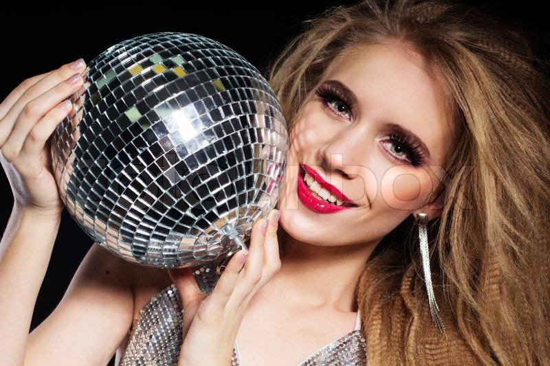Fashion portrait of smiling girl wearing glamour clothes with disco ball over black background, stock photo