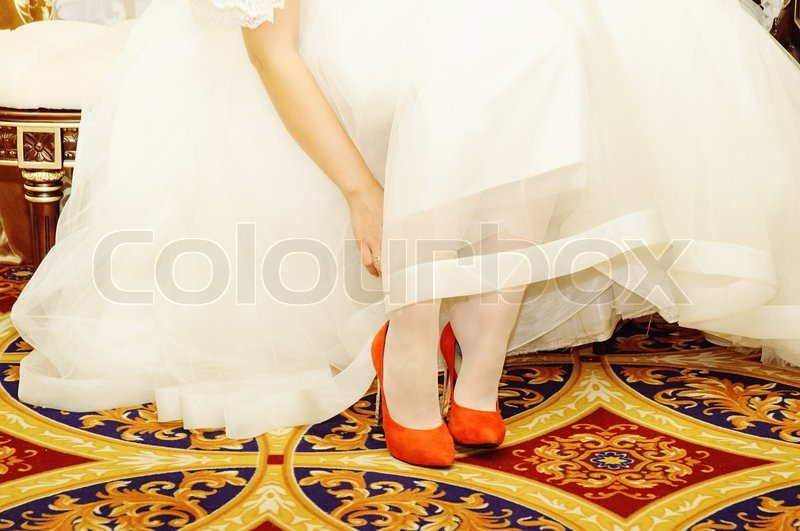 Stock image of 'Young bride wears red shoes'