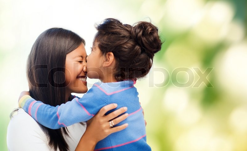 Family, children and happy people concept - happy little girl hugging and kissing her mother over green background, stock photo