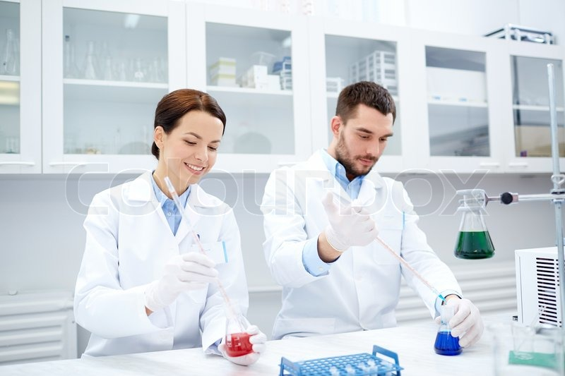 Science, chemistry, technology, biology and people concept - young scientists with pipette and flask making test or research in clinical laboratory, stock photo