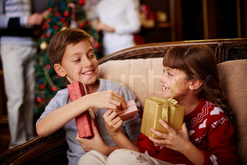 Glad boy and girl with Christmas presents in boxes, stock photo
