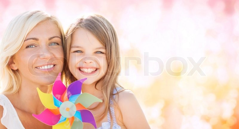 Summer holidays, family, children and people concept - happy mother and girl with pinwheel toy over pink lights background, stock photo