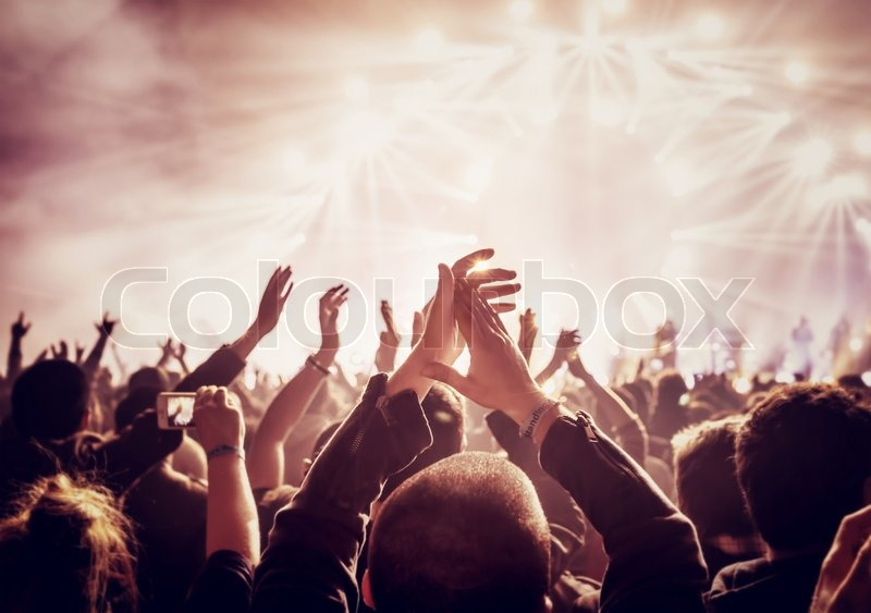 Vintage style photo of a crowd, happy people enjoying rock concert, raised up hands and clapping of pleasure, active night life concept, stock photo