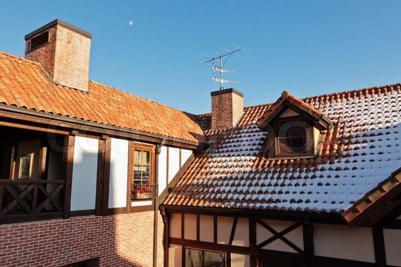 House With Chimney : Tiled roof of a european house with chimney antenna and