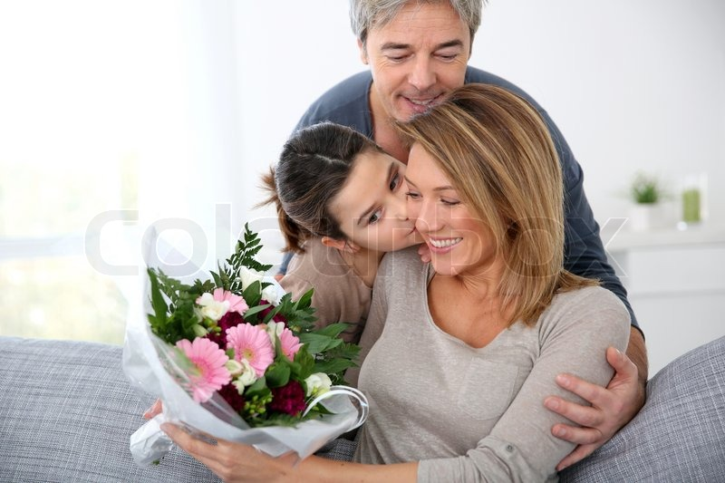 Family celebrating mother\'s day with bunch of flowers, stock photo