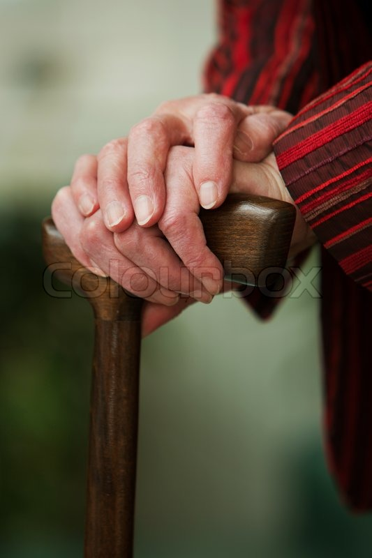 Stock image of 'The hands of an old woman holding a walking stick'