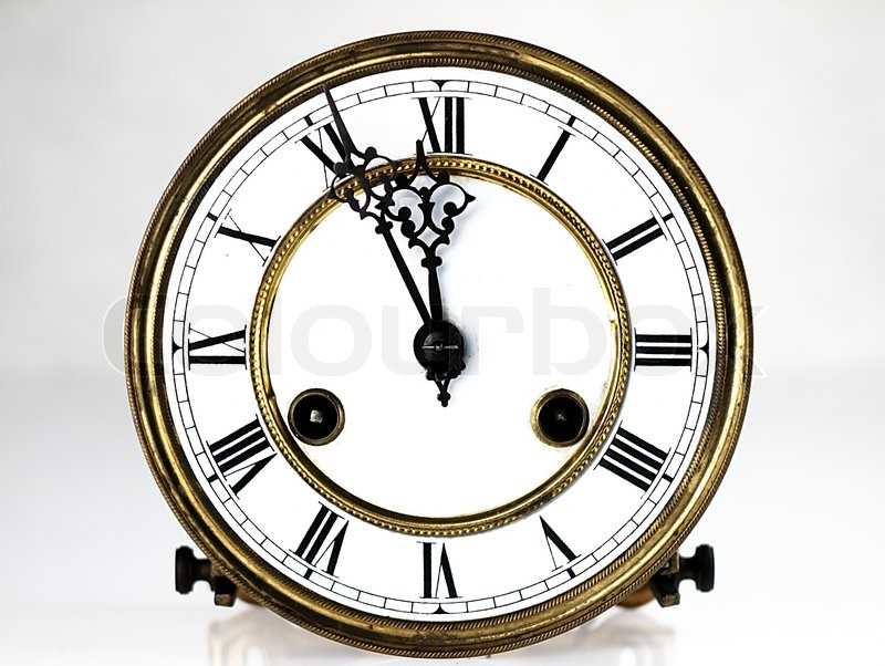 Mechanism of old clock. Clock face and hands showing five minutes to midnight, stock photo