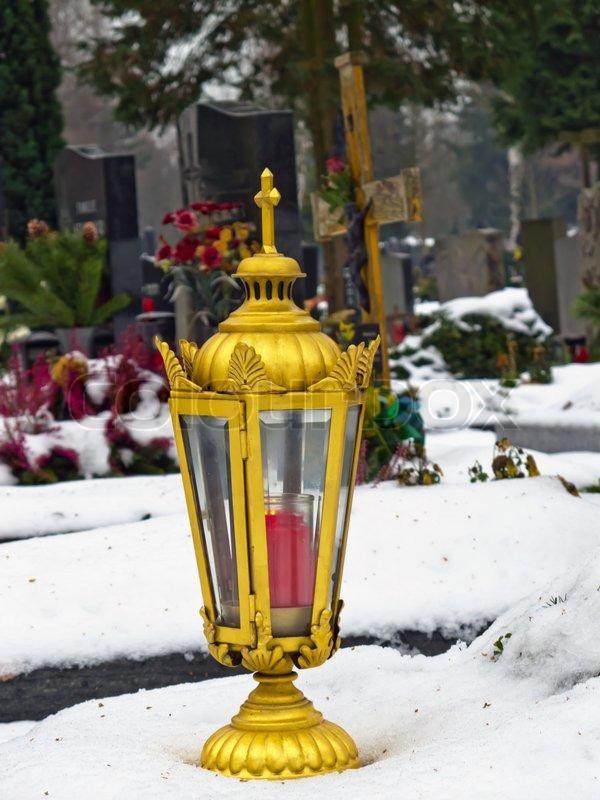 eine goldene lampe steht auf einem schneebedeckten grab im. Black Bedroom Furniture Sets. Home Design Ideas