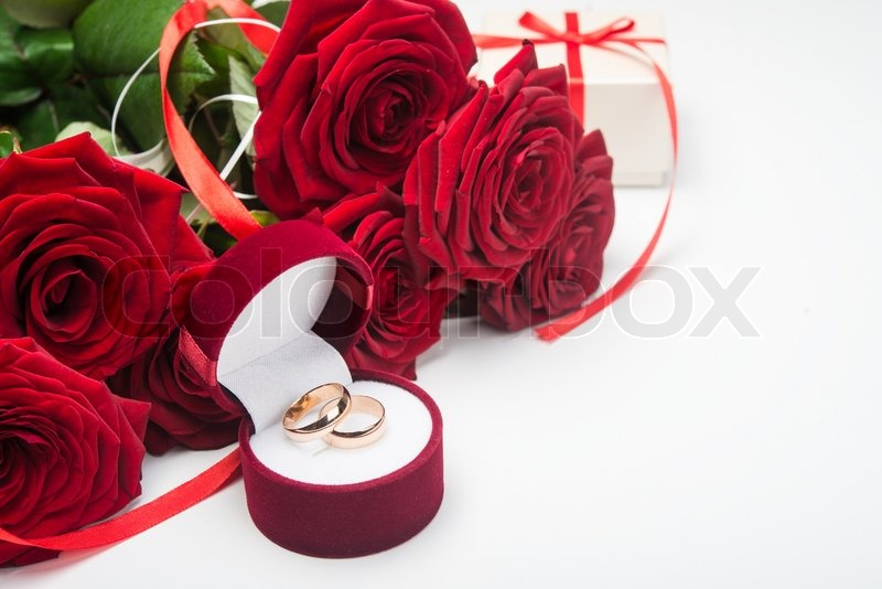 romantic red roses with wedding rings valentine day background stock photo colourbox