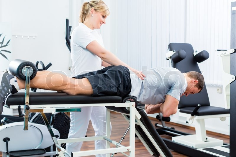 Patient at the physiotherapy doing physical exercises with therapist ...