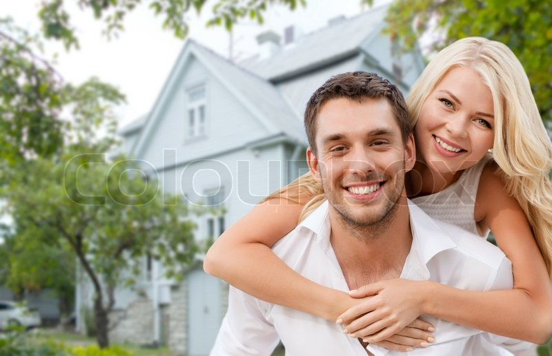 Love, people, real estate, home and family concept - smiling couple hugging over house background, stock photo