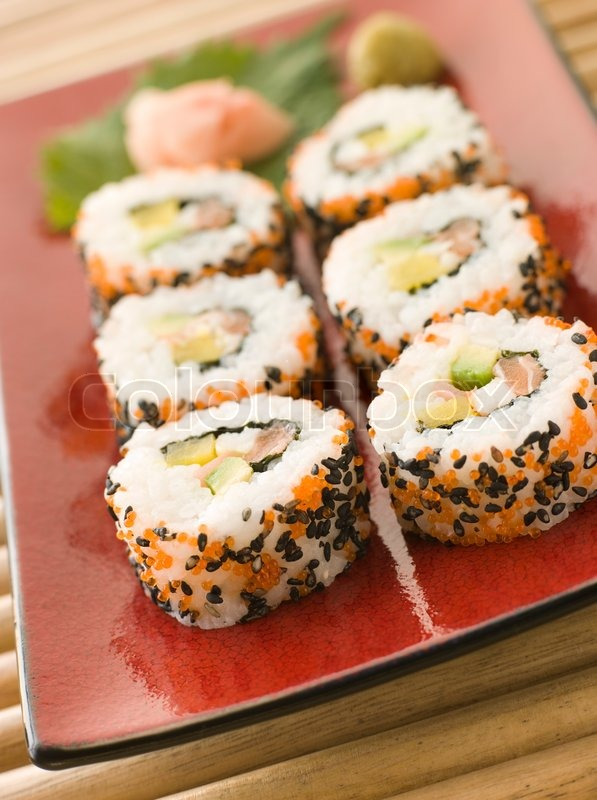Plate of Inside-out Sushi Rolls decorated with roe and sesame seeds, stock photo
