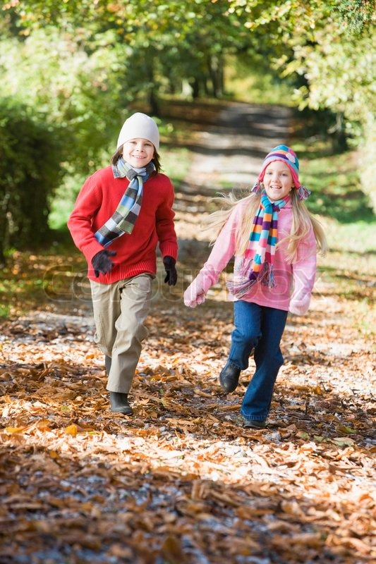 Stock image of 'Young boy running along autumn path through woods'