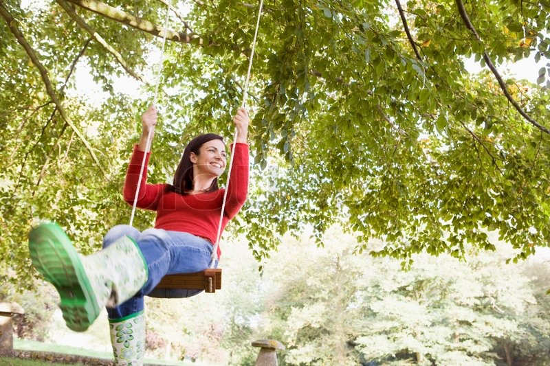 Young Woman On Garden Swing Stock Photo Colourbox