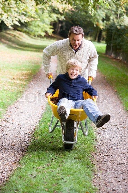 Father Giving Son Ride In Wheelbarrow Stock Image