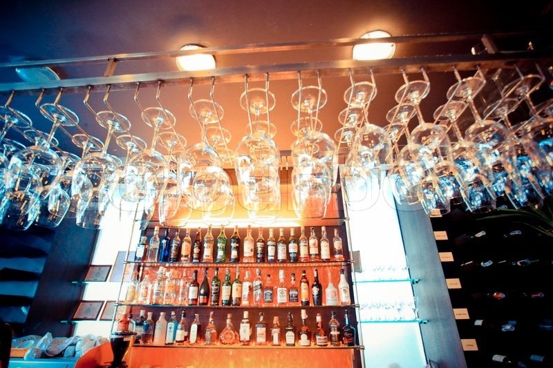 Empty glasses hanging at the bar and Bar with bottles Blurred Background, stock photo