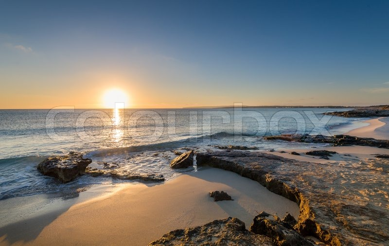 Sun is rising at the horizon and lit sand beaches of Formentera island. Spain, stock photo