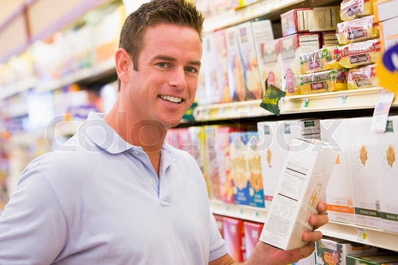 Stock image of 'Young man grocery shopping in supermarket'
