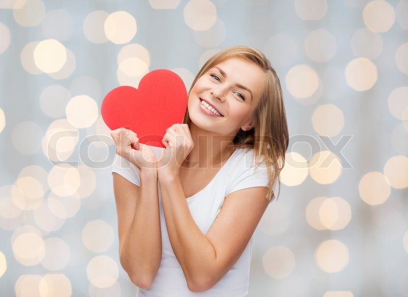 Happiness, health, people, holidays and love concept - smiling young woman in white t-shirt holding red heart over lights background, stock photo