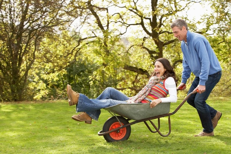 paar mit mann giving frau ride in schubkarre stockfoto colourbox. Black Bedroom Furniture Sets. Home Design Ideas