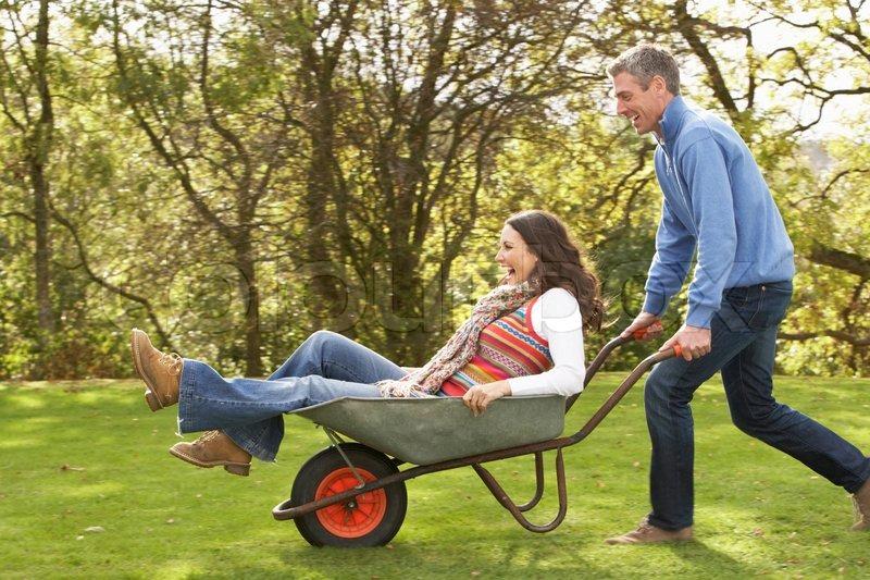 Couple With Man Giving Woman Ride In Wheelbarrow | Stock ...