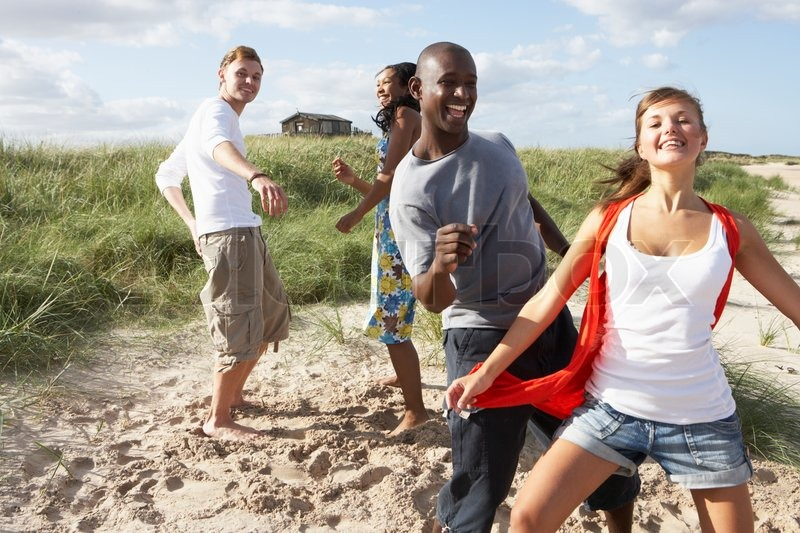 group of young people having fun dancing on beach together stock