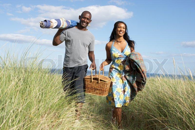 Young Couple Carrying Picnic Basket And Windbreak Walking Through Dunes, stock photo