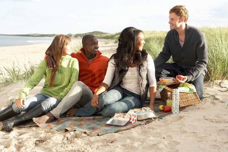 Group Of Young Friends Enjoying Picnic On Beach Together ...