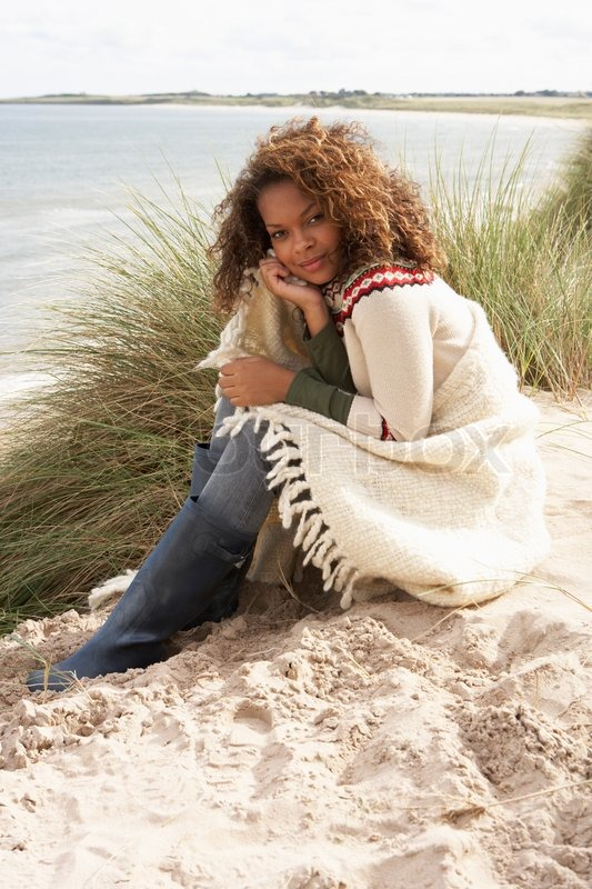 Young Woman Sitting In Sand Dunes Wrapped In Blanket, stock photo