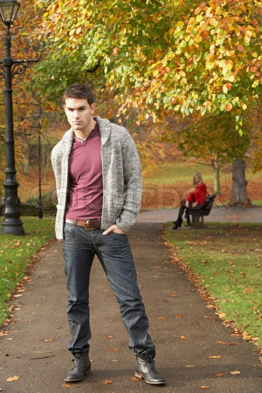 Teenage Boy Standing In Autumn Park With Female Figure On