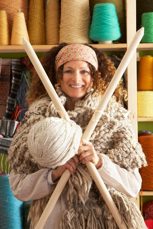 Giant Knitting Needles And Wool Uk : Woman wearing knitted scarf standing in front of yarn