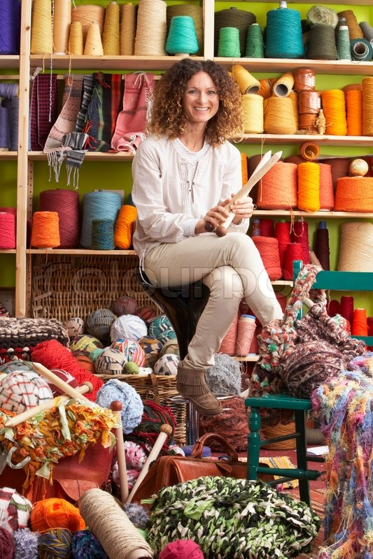 Stock image of 'Woman Sitting On Stool Holding Knitting Needles In Front Of Yarn Display'
