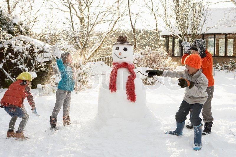 Mother And Children Building Snowman In Garden | Stock Photo ...