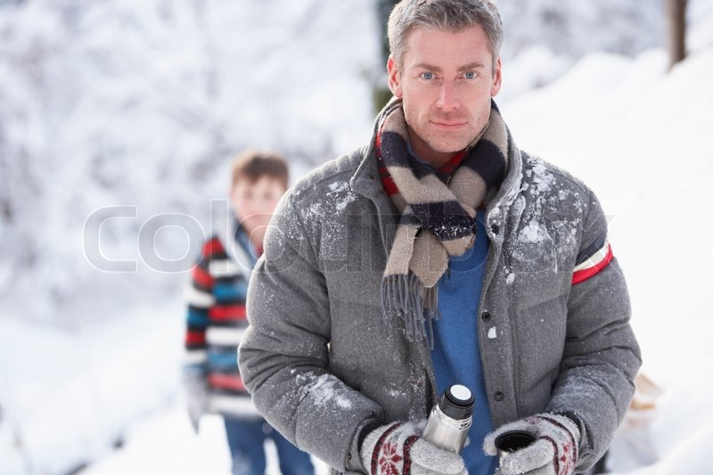 Family Stopping For Hot Drink And Snack On Walk Through Snowy Landscape, stock photo