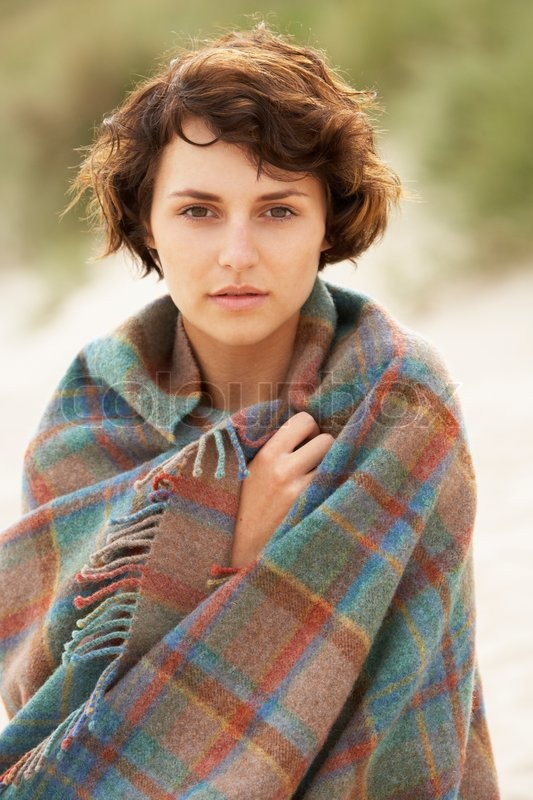 Young Woman Standing In Sand Dunes Wrapped In Blanket, stock photo