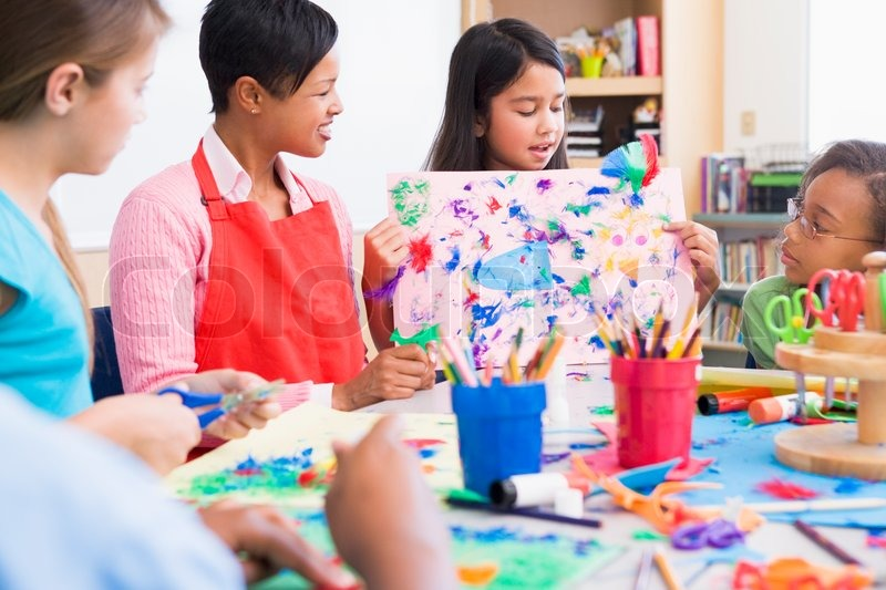 Elementary school pupil in art class showing picture to for Art and craft classes for kids