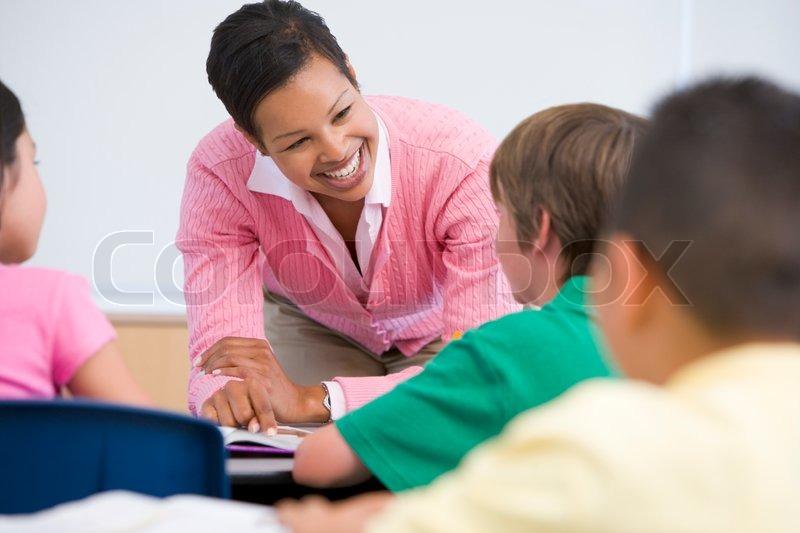 Elementary school teacher with pupils in classroom, stock photo