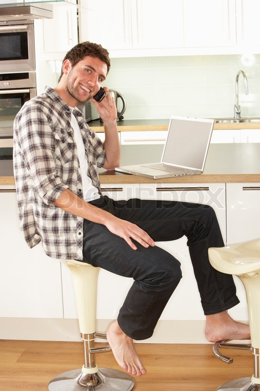 Young Man Relaxing Sitting In Kitchen Talking On Phone | Stock Photo |  Colourbox
