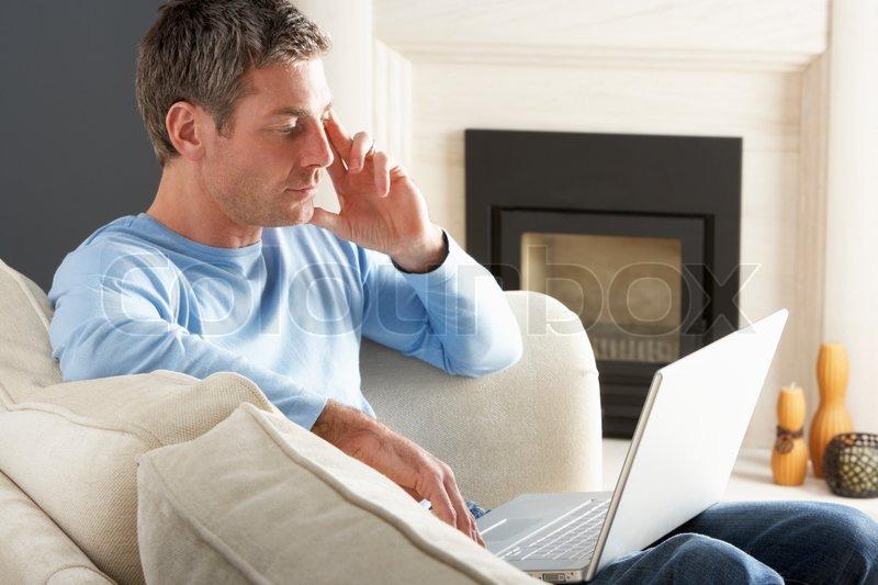 mann mit laptop erholungsurlaub sitzt auf sofa zu hause stockfoto colourbox. Black Bedroom Furniture Sets. Home Design Ideas