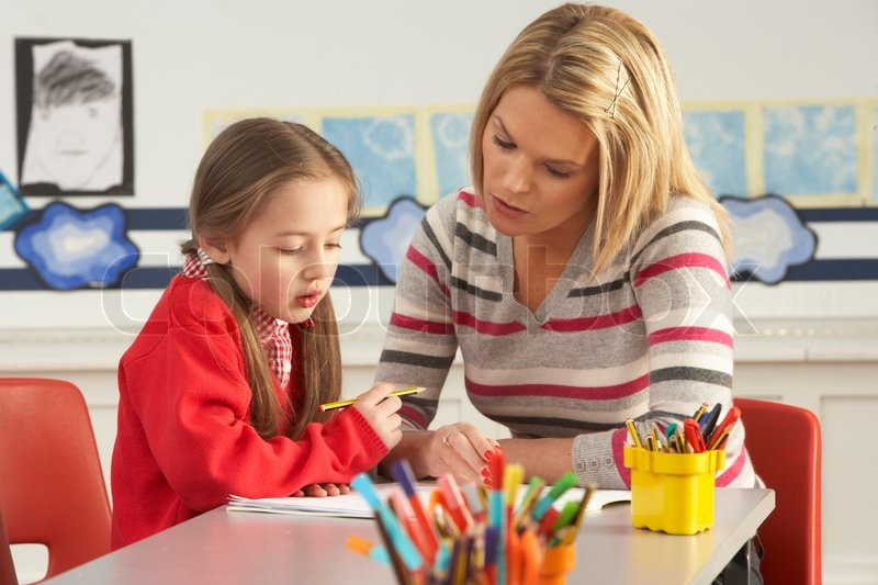 female primary school pupil and teacher working at desk in classroom stock photo colourbox
