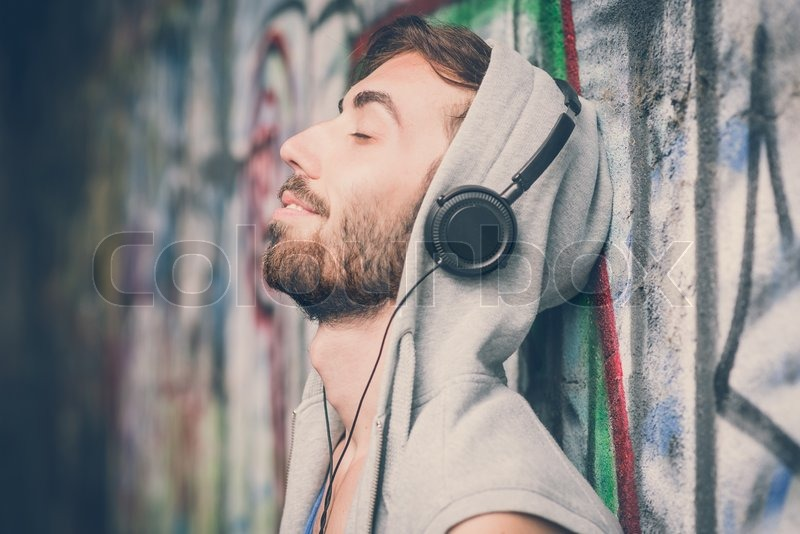 Young hipster gay man listening music headphones, stock photo