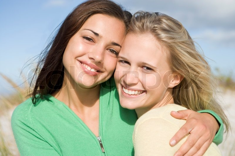 fbd1f709d2 Two young women embracing at beach