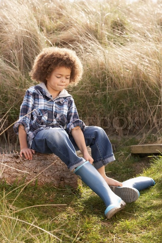 young boy putting on gummistiefel stock foto colourbox. Black Bedroom Furniture Sets. Home Design Ideas