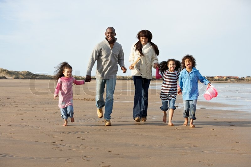 Portrait Of A Black Family Smiling While Running On Beach