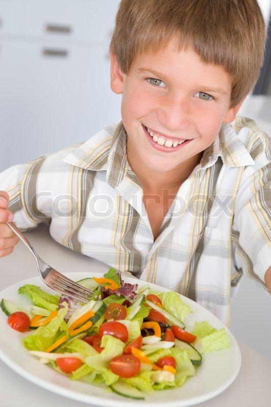 boy sitting at table eating salad at