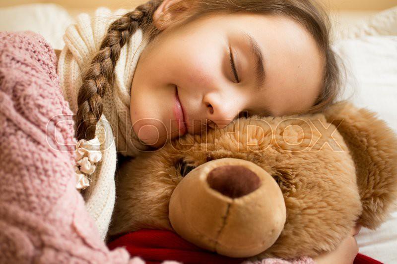 Closeup portrait of little girl sleeping on brown teddy bear, stock photo
